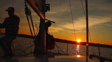 Dusk at sea, crew working on sailing yacht, coming home