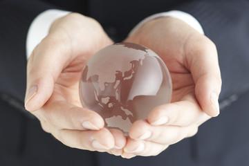 ガラスの地球を持つビジネスマンの手