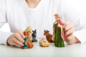 A boy holds the statues of The Holy Family in a Christmas Crib