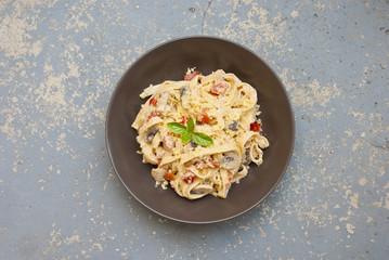 Fresh pasta with mushrooms on vintage background