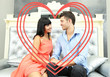 Beautiful young romantic couple and heart-shaped frame sitting