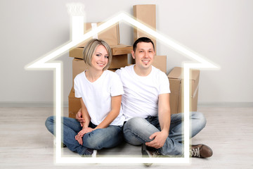 Young couple surrounded by form of house