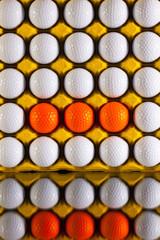 Golf balls in paper carton for eggs
