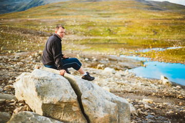 Man Sitting On Stone In Norwegian Mountains
