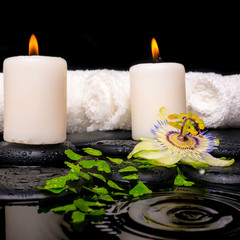 spa setting of passiflora flower, green branch fern, towels and