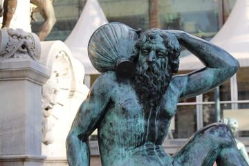 Statue of a man carrying a demijohn in Innsbruck, Austria