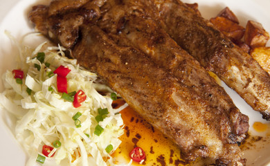 close up spare ribs with salad and fried potato