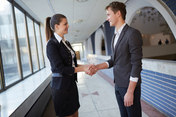 Young business woman and businessman talking in the hallway