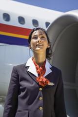 Italy, flight stewardess near an airplane