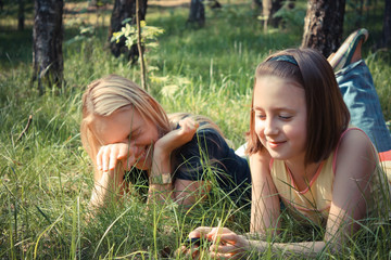 Girl with her mommy having fun on grass