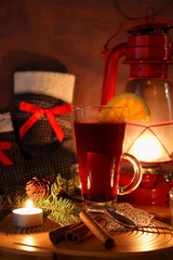 A cup of mulled wine and Christmas socks with gifts.