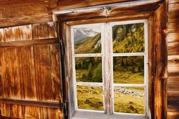 herbstliche Almlandschaft im Holzfenster der Almhütte