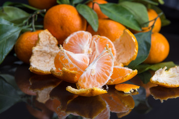 mandarin or tangerine with leaves and branches on a black marble