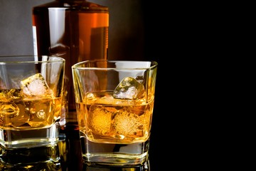 whiskey in glasses in front of bottle on black background