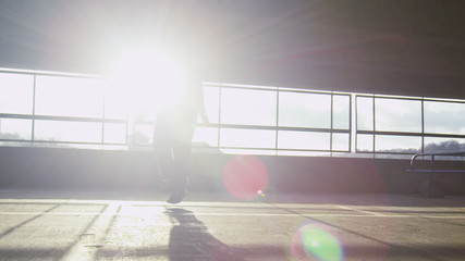 Slow motion tracking shot of man skipping in the sunlight