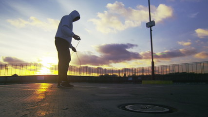 Hooded man skipping outside with the low sun behind him