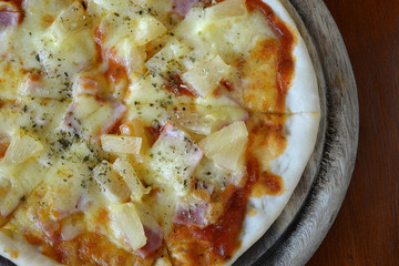 Hawaiian Pizza with pineapple , ham and cheese top view