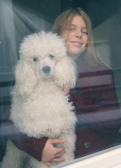 Little girl and her dog looking out the window,vintage photo