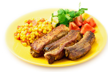 The pork chops with roasted corn on the yellow plate