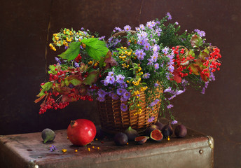 Fig, a pomegranate and a basket with flowers