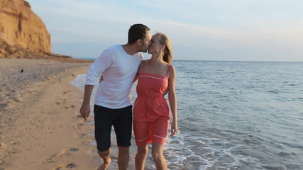 Loving couple of young parents walking along the coast with