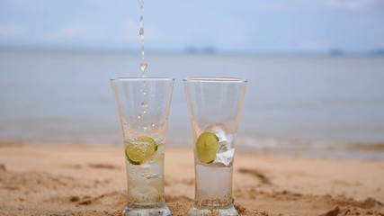 Pouring Ice Cold Tea with Lime Slices in Glasses on Beach.