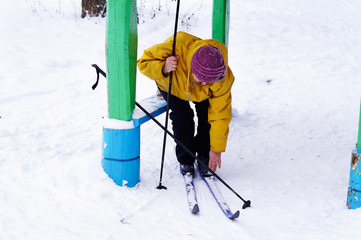 An old woman puts on skis in the forest