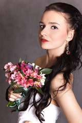 Portrait of a young beautiful fiancee with a bunch of flowers