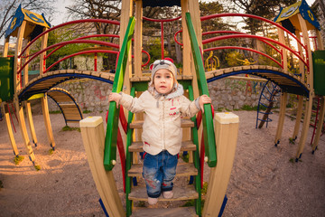Cute little girl on the colorful playground