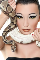 Portrait of a beautiful girl with a snake in his hands near face