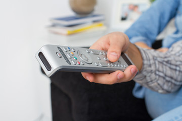 Closeup of hand with remote control at home