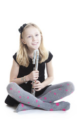 young smiling blond girl holds flute in studio sitting down