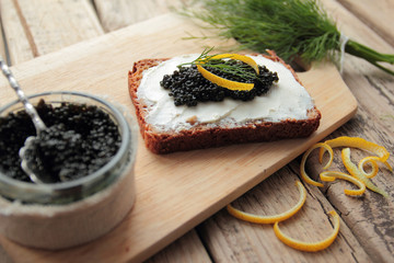 Black caviar and cream cheese on cutting bread
