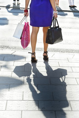 Young shopping woman crossing street
