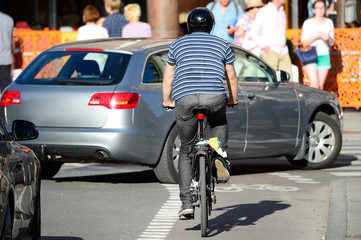 Man with helmet bicycling in traffic