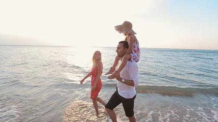 Happy family walking along the beach barefoot