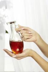 Hände mit einem Flacon Massageöl