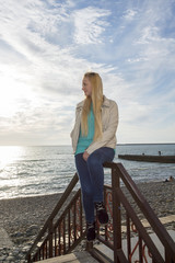 Beautiful blonde looks at the sea.