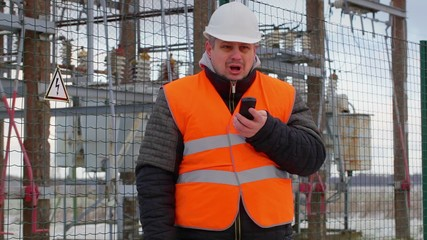 Angry Electrical Engineer talking on cell phone in  substation