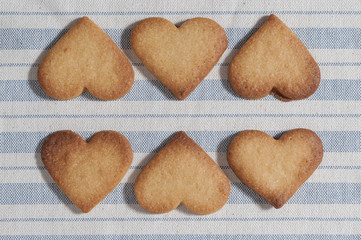 Butter cookies, heart shaped, on a striped fabric napkin