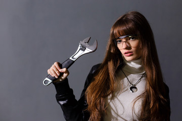 Girl in safety glasses with adjustable wrench on a dark backgrou