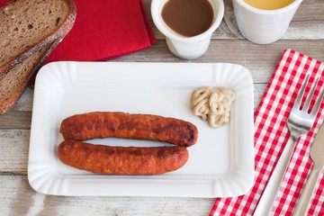 Bratwurst with mustard for breakfast, with drinks, top view