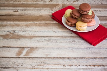 Macarons on plate, on wooden table, space on bottom left