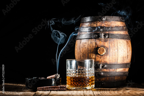 Fotobehang Bar Glass of alcohol and smoking noble cigar on a black background