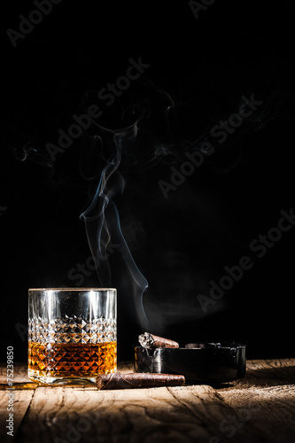 Foto op Canvas Bar Glass of alcohol and smoking noble cigar on a black background