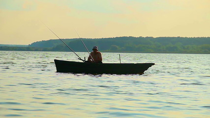 Silhouette of lone fisherman sitting in boat, fishing equipment
