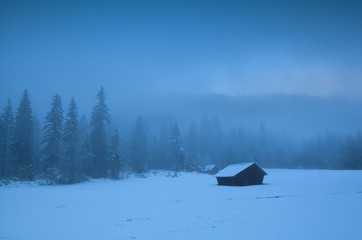 wooden huts in fog and snow