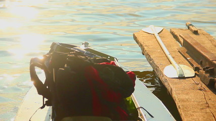 Tourist backpack in canoe at sunset. Tourism, traveling, holiday