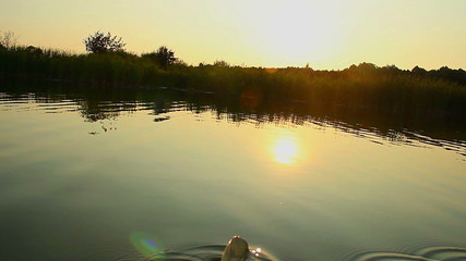 Person paddling boat, enjoying beautiful sunset on river, POV