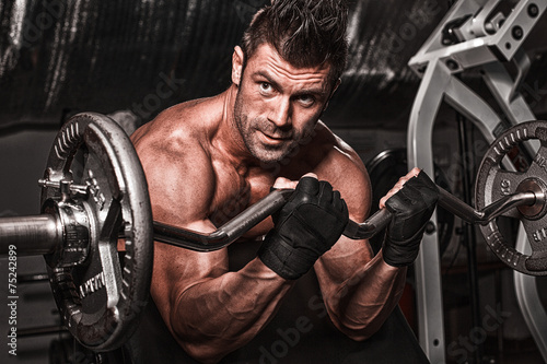 Closeup of a muscular young man lifting weights on dark backgrou